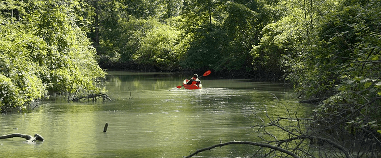 A fishing kayak going down the river.