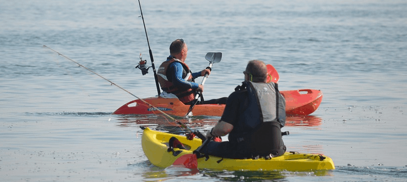 2 men with fishing kayaks and gear.